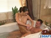 Horny brunette masseuse blows cock in bathtub